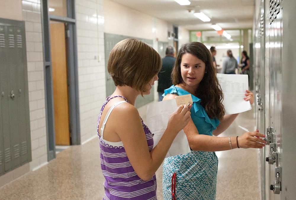 Dedham, MA 08/30/2011.Freshman Danielle Letsche gets some help with her locker combination from math teacher Tara Fountain during Tuesday's Freshman orientation at Dedham High School.
