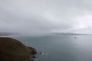 Landscape looking out to sea at Dinas Head as a ship passes as rain comes in near Newport, Pembrokeshire, Wales, United Kingdom.