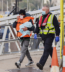 © Licensed to London News Pictures. 14/04/2021. Dover, UK. A migrant is helped ashore by a Border Force officer at Dover Harbour in Kent after crossing the English Channel. Home Secretary Priti Patel has pledged an overhaul of asylum seeker rules, with refugees having their claim assessed based on how they arrive in the UK. Photo credit: Stuart Brock/LNP