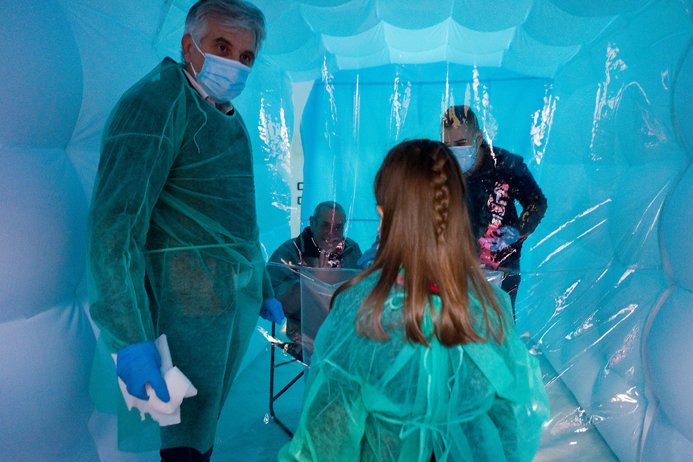 A father and his daughter wearing protective suits against the spread of the novel coronavirus COVID-19 meet a relative through a plastic sheet installed in a special 'hug room' organised to keep people safe from COVID-19 infection at a care home in Santa Lucia di Serino, province of Avellino, southern Italy, on January 2, 2021.