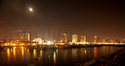 Israel, Tel Aviv skyline and yacht marina at night as seen from west