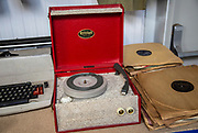 A Dansette Popular mono portable record player on sale at auction next to 78 rpm records