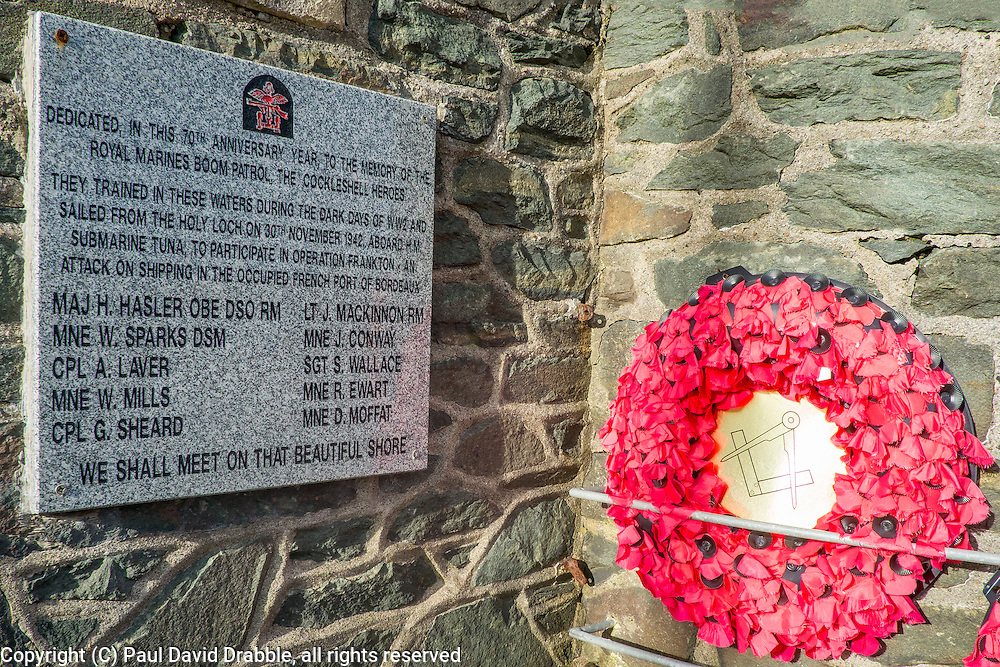 """The war memorial, in the form of a large round tower, is situated at Lazaretto Point on the southwest shore of the Holy Loch between Ardnadam and Sandbank. Built during the 1920s, to commemorate those who fell in World War One. A bronze plaque was later added to the front of the tower and marks the sacrifice of the """"officers and men of the Sandbank and district who died in their country's service"""" during the Second World War.<br /> On a low wall to the towers left is a polished stone marker baring the black and red badge of the Combined Operations. erected to mark the 70th anniversary of Operation Frankton the memorial is dedicated to the memory of """"The Royal Marines boom patrol, The Cockleshell Heroes"""" who sailed from Holy Loch to take part in the operation. <br /> <br /> 04 April  2015<br /> Image © Paul David Drabble <br /> www.pauldaviddrabble.co.uk"""
