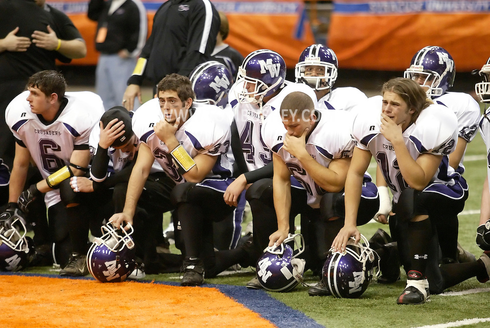 Monroe-Woodbury players kneel during the awards ceremony following their 27-26 overtime loss to Auburn in the Class AA state championship game at the Carrier Dome in Syracuse on Nov. 25, 2006.