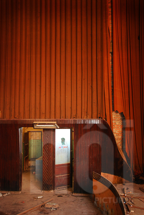 Abandoned cinema of Bouasavanh, Vientiane, Laos, Asia. Red curtains fall down on the walls. Entry of toilets.