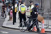 Andrew Mitchell MP, pushes his bike past police officers outside parliament during the Coronavirus pandemic, on 16th September 2020, in London, England. Andrew John Bower Mitchell is a British politician who has been Member of Parliament for Sutton Coldfield since 2001.