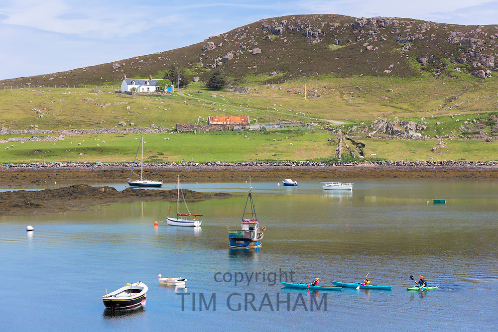 Family outing, father and children paddling kayaks in Old Dornie Harbour near the Summer Isles, on West Coast of Scotland