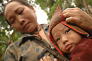 """Ms. Mee Moua Vang, with her baby, Li Cheng Vang, near Vang Vieng, Laos, July 4, 2006.  Her message  to the world, """"My husband and two older daughters were killed by the communist while foraging for food.  My daughter Blee was attacked by the communist where her guts were sticking out and I was unable to help her so she died.  I miss her very much.  I am desperately suffering here with no help.  I ask you to come in and save us.  Bring us food.""""..**EXCLUSIVE, no tabloids without permission**"""