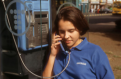 Young girl using public telephone,