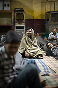 Homeless men watch television in the Fatepuri night shelter for the homeless in Old Delhi, India.