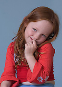 A shy 4 year old girl with finger in mouth