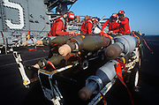 Red-shirted US Navy ordnance crewmen prepare to fit smart bombs and missiles to an F/A-18 fighter jet on the deck of US Navy aircraft carrier USS Harry S Truman during its deployment patrol of the no-fly zone at an unknown location in the Persian Gulf, on 8th May 2000, in the Persian Gulf. The Truman is the largest and newest of the US Navys fleet of new generation carriers, a 97,000 ton floating city with a crew of 5,137, 650 are women.