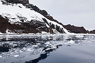 Reflections along the mixed rock and ice cliifs of the coastline in very still conditions on approach to Peter 1 Øy by Zodiac, Phantom Coast, Western Antarctica