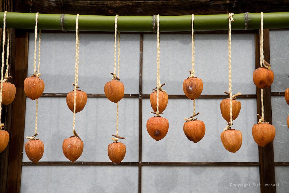 Persimmon fruit (kaki) drying outdoors at Gassho Village of Gero Onsen, an open air museum, Gero City, Gifu Prefecture, Japan