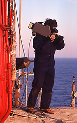 Stock photo of a videographer filming aboard an offshore drilling rig