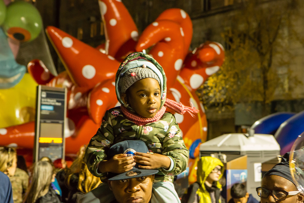 "New York, NY – 27 November 2019. Thousands of spectators packed the streets around the American Museum of Natural History to see the inflation area for the balloons for Macy's Thanksgiving Day Parade. A girl rides on her father's shoulders in front of Yayoi Kusama's ""Love flies up to the sky."""