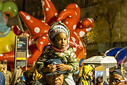 """New York, NY – 27 November 2019. Thousands of spectators packed the streets around the American Museum of Natural History to see the inflation area for the balloons for Macy's Thanksgiving Day Parade. A girl rides on her father's shoulders in front of Yayoi Kusama's """"Love flies up to the sky."""""""