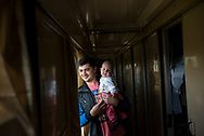 Andrei holds his six-month-old daughter Nicole near the end of a 20-hour train journey from Mariupol to Kiev in Ukraine. (September 27, 2015)