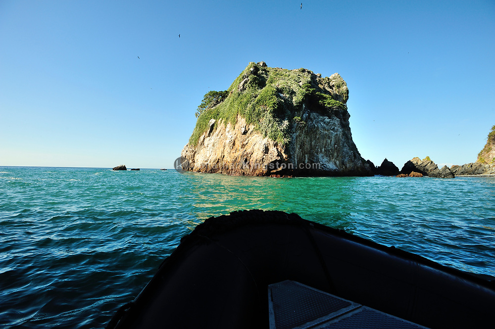 The bow of a small inflatable boat in the blue green waters of Bona Island, off the pacific coast of Panama.