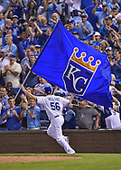 Kansas City Royals pitcher Greg Holland (56) carries the Royals flag and celebrates with fans after a walk off win over the Oakland Athletics in the 2014 American League Wild Card playoff baseball game at Kauffman Stadium.