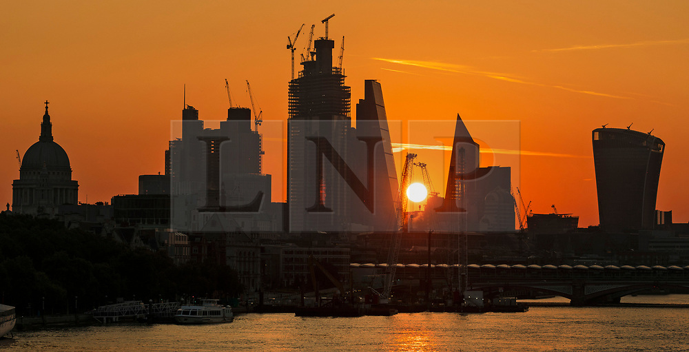 © Licensed to London News Pictures. 01/09/2018. London, UK.  Sunrise on the River Thames, seen behind City of London skyscrapers on the first day of meteorological autumn.  Photo credit: Vickie Flores/LNP