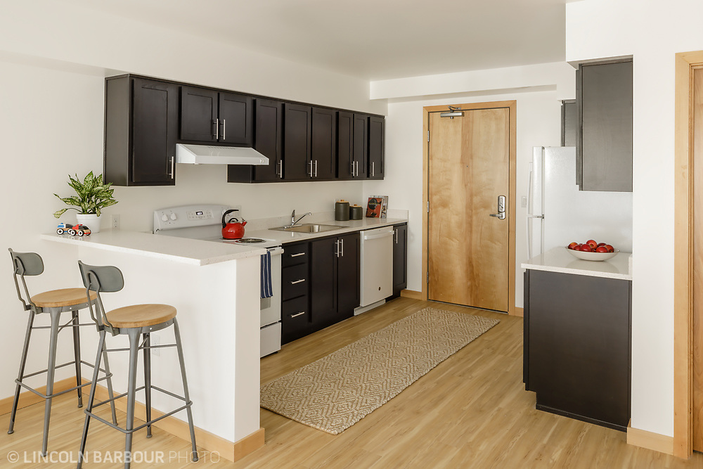 A kitchen with a bar inside of an affordable housing apartment building.