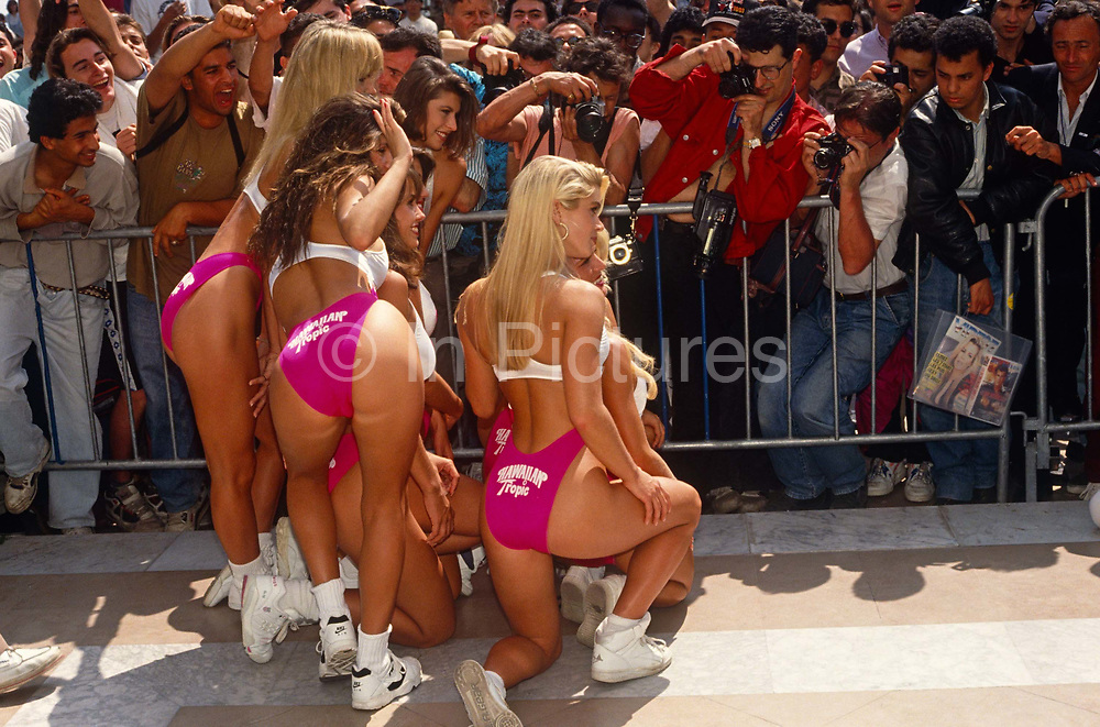 During the Cannes Film Festival, we see a group of girls from the Hawaiian Tropic sun cream company posing in bikinis and revealing swim wear for a frenzy of males of various ages on La Croisette, Cannes sea front in the French Riviera resort, Cote d'Azur. They pose in the same corporate style for photographers around the world but here, young women publicising movies or just themselves, regularly strut along the beaches and pavements of this French town. The weather is typically bright for May with clear skies and high temperatures. Cannes  is a major tourist centre and a leading resort on the French Riviera. Located in the Alpes-Maritimes région, Founded in 1939, the International Film Festival is one of the world's most prestigious and eccentric of celebrations of film and the cinema industry.