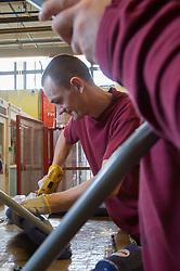A prisoner welding in a prison workshop making prison chairs