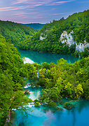 Plitvice Lakes National Park is one of the oldest national parks in Southeast Europe and the largest national park in Croatia. In 1979, Plitvice Lakes National Park was added to the UNESCO World Heritage register. The national park was founded in 1949 and is situated in the mountainous karst area of central Croatia, at the border to Bosnia and Herzegovina. The important north-south road connection, which passes through the national park area, connects the Croatian inland with the Adriatic coastal region.<br /> <br /> The national park is world famous for its lakes arranged in cascades. Currently, 16 lakes can be seen from the surface. These lakes are a result of the confluence of several small rivers and subterranean karst rivers. The lakes are all interconnected and follow the water flow. They are separated by natural dams of travertine, which is deposited by the action of moss, algae, and bacteria. The particularly sensitive travertine barriers are the result of an interplay between water, air and plants. The encrusted plants and bacteria accumulate on top of each other, forming travertine barriers which grow at the rate of about 1 cm (0.4 in) per year.<br /> <br /> The lakes are renowned for their distinctive colors, ranging from azure to green, grey or blue. The colors change constantly depending on the quantity of minerals or organisms in the water and the angle of sunlight.