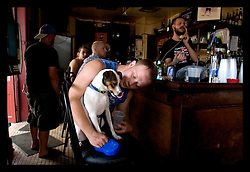 """3rd Sept, 2005. Hurricane Katrina aftermath. New Orleans. Johnny White's Sports Bar on Bourbon Street in the French Quarter - with it's claim to """"Never Close."""" The bar has remained open throughout. John Webster gives his dog Muffin a drink at the bar."""