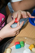 Marzipan workshop. Child forming shapes from coloured Marzipan. Model release available