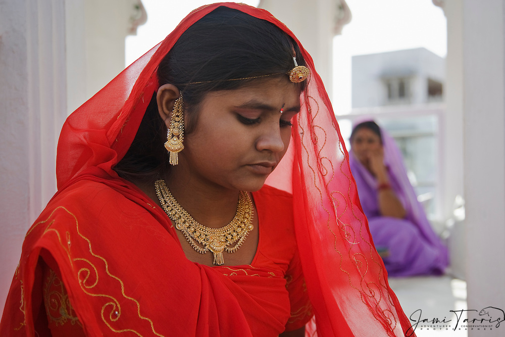 A serious young girl in a red sari in the blue city of Jodphur, Jodphur Rajasthan, India
