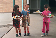 "Getting a little help from her friends.  Meghan Clifford, center, is assisted by Destini Hamilton, left and Chrystina Granvold with her lunch tray at Cameron Ranch Elementary School in Carmichael.  Meghan, 8, is in the first grade as a ""full inclusion"" student despite her physical and mental disabilities. May 29, 1998."