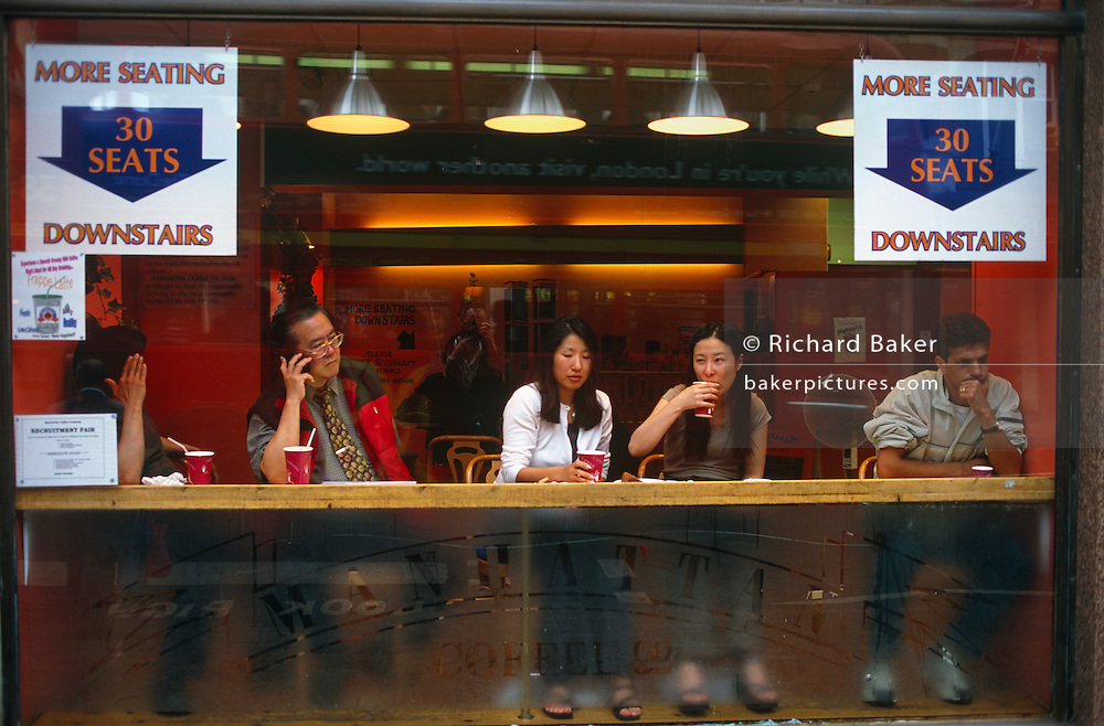 Five customers are seated in the window of the Manhattan Coffee Company on Shaftesbury Avenue, in London's Chinatown. 3 of the 5 are of Chinese ethnicity, one is talking on a mobile phone and the other two seem to be girlfriends. To their left is a man in deep thought but in front of every person there are red beakers. It is a successful shop with plenty of customers. The interior lighting is orange and red, making a cosy and welcoming atmosphere and two large signs in English indicate there are 30 more seats downstairs allowing more to spend their money and for more business to be made.