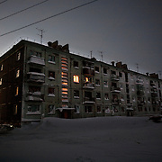 In this apartment block on the edge of the tundra  outside Vorkuta town, only one family is left..Buildings around Vorkuta are being surrendered to the Arctic elements as people flee to the south of Russia. .Vorkuta is a coal mining and former Gulag town 1,200 miles north east of Moscow, beyond the Arctic Circle, where temperatures in winter drop to -50C. .Here, whole villages are being slowly deserted and reclaimed by snow, while the financial crisis is squeezing coal mining companies that already struggle to find workers..Moscow says its Far North is a strategic region, targeting huge investment to exploit its oil and gas resources. But there is a paradox: the Far North is actually dying. Every year thousands of people from towns and cities in the Russian Arctic are fleeing south. The system of subsidies that propped up Siberia and the Arctic in the Soviet times has crumbled. Now there's no advantage to living in the Far North - salaries are no higher than in central Russia and prices for goods are higher.