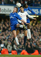 Photo: Scott Heavey<br />Chelsea V Tottenham Hotspur. 01/02/03. <br /> Marcel Desilly and Emmanuel Petit fight in the air with ex chelsea player Gustavo Poyet during this premiership clash at Stamford Bridge.