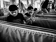 """29 MARCH 2017 - BANG KRUAI, NONTHABURI, THAILAND: People sit in their coffins during their ritualistic rebirth during a """"Resurrection Ceremony"""" at Wat Ta Kien (also spelled Wat Tahkian), a Buddhist temple in the suburbs of Bangkok. People go to the temple to participate in a """"Resurrection Ceremony."""" Groups of people meet and pray with the temple's Buddhist monks. Then they lie in coffins, the monks pull a pink sheet over them, symbolizing their ritualistic death. The sheet is then pulled back, and people sit up in the coffin, symbolizing their ritualist rebirth. The ceremony is supposed to expunge bad karma and bad luck from a person's life and also get people used to the idea of the inevitability of death. Most times, one person lays in one coffin, but there is family sized coffin that can accommodate up to six people. The temple has been doing the resurrection ceremonies for about nine years.          PHOTO BY JACK KURTZ"""