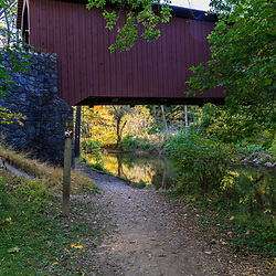 walking trail leads under a covered bridge..