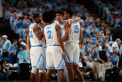 CHAPEL HILL, NC - FEBRUARY 05: Kenny Williams #24, Coby White #2, and Garrison Brooks #15 of the North Carolina Tar Heels huddle during a game against the North Carolina State Wolfpack on February 05, 2019 at the Dean Smith Center in Chapel Hill, North Carolina. North Carolina won 113-96. North Carolina wore retro uniforms to honor the 50th anniversary of the 1967-69 team. (Photo by Peyton Williams/UNC/Getty Images) *** Local Caption *** Kenny Williams;Coby White;Garrison Brooks