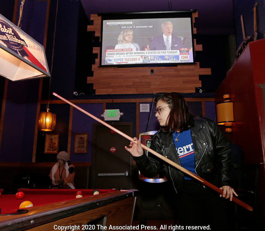 Rubyna Ali plays pool with at an informal campaign party for Democratic presidential candidate Sen. Bernie Sanders, I-Vt. with Democratic presidential candidate former Vice President Joe Biden on the television behind while waiting for the results come in for the Washington State primary, Tuesday, March 10, 2020, in Seattle. (AP Photo/John Froschauer)