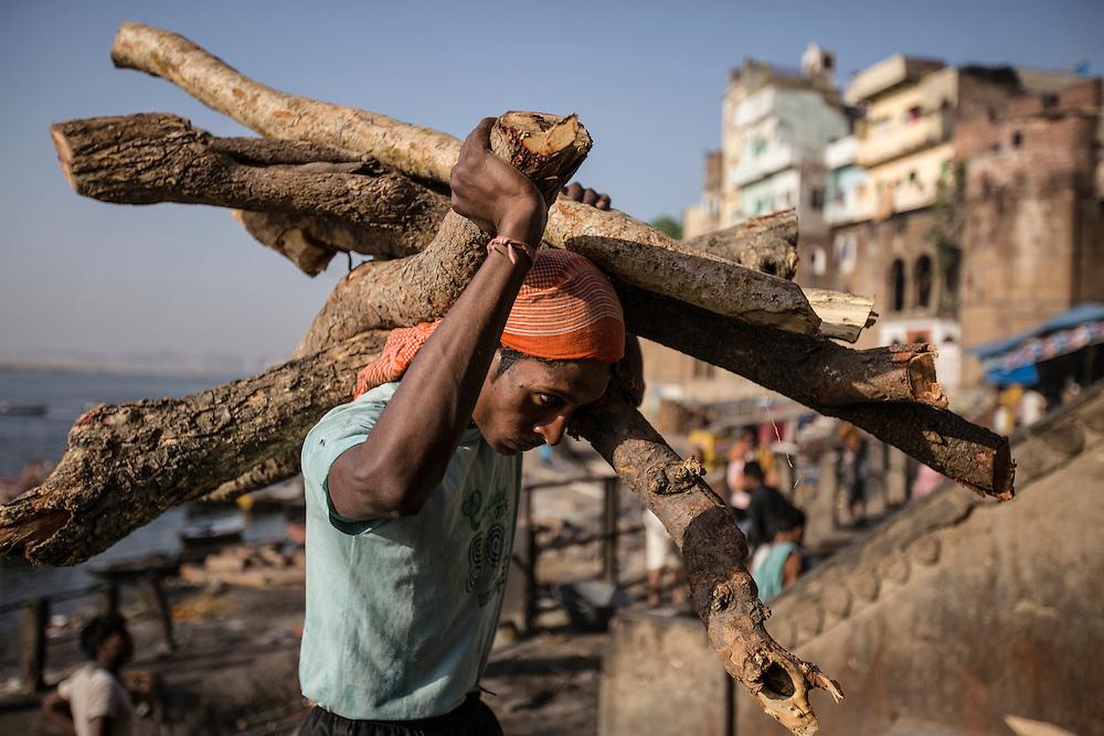 Un travailleur Dom transporte du bois sur Manikarnika ghat