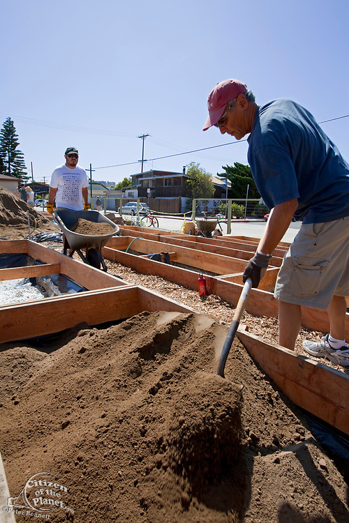 July 24, 2010. Laying down the soil for the final preparations of the planting beds at the Venice Community Garden. The 2 foot deep beds are layered with 3 inches of rocks as a buffer between the roots and the bad soil below, but will still allow water to drain. White Gypsum powder is spread on top of the rocks and then watered to break down the soil particles and hard clay below for better drainage and to enable aeration by worms and microorganisms. Plastic sheeting is stapled around the sides of the beds to keep toxins (such as the arsenic and lead found in the soil samples), to leach into the soil during rains. Weed cloth is then stapled around the beds to prevent the roots from tearing a hole in the plastic sheeting and accessing the toxic soil on the outside. For the planting soil, a 50/50 mix of organic matter and city compost is layered on top of the rocks, and beds are now ready for planting. The Venice Garden broke ground in April, 2010. Soil tests revealed high levels of arsenic and lead because of previous uses which included a railroad line going through the lot. Steps were taken which included adding protective layers and adding new soil. Planting began in August and the first harvest was in October, 2010. Venice, California, USA