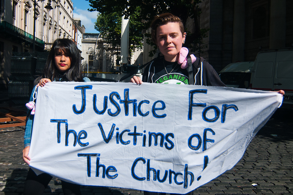 """Dublin, Ireland. 25th August, 2018. <br /> Irish survivors show a sign with a message asking justice fot the victims of the Catholic Church during the first of the two-days of the visit of Pope Francis in Dublin, Ireland.<br /> Pope Francis has made a two-day visit to the Republic of Ireland by celebrating a Mass at Dublin's Phoenix Park. The Argentine Pope asked forgiveness for the """"abuses in Ireland, abuses of power, conscience and sexual abuses"""" perpetrated by Church leaders. It was the first papal visit to Ireland for 39 years. During his activities many activists, victims and survivors have made protests and a silent march Garden of Remembrance towards the last Magdalene Laundry to close in Ireland.<br />  © Simone Padovani"""