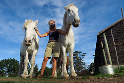 South Africa - Plettenberg Bay - 21 May 2020 - Pictured is Debbie Fermor with 2 of her rescue horses. Hog Hollow Horse Trails is based on Askop Road, The Crags, and offer trails on horseback through magnificent natural beauty to attractions in the area, including wine farms, Animal Sanctuaries and a picnic spot on the spectacular Kurland Estate. The horses are rescue horses. Their Horse Drawn Carriage tours are based at Kay and Monty Wine Estate on Redford Road, and offer trails in a vintage horse drawn carriage between two boutique wine estates to enjoy wine tastings, cellar tours and an optional tappas style lunch. South Africa is currently under lockdown in an attempt to flatten the curve to halt the spread of the COVID-19 coronavirus pandemic. Picture: David Ritchie/African News Agency(ANA)