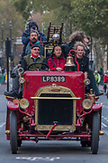 A vintage fire engine driving down Whitehall - Bonhams London to Brighton Veteran Car Run celebrates the 122nd anniversary of the original Emancipation Run of 1896 which celebrated the passing into law the Locomotives on the Highway Act so raising the speed limit for 'light automobiles' from 4mph to 14mph and abolishing the need for a man to walk in front of all vehicles waving a red flag. The Movember Foundation as our Official Charity Partner.