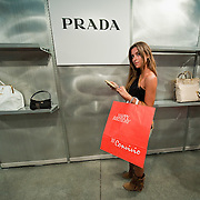 MILAN, ITALY - JUNE 11:  A customer chooses a purse in front of shelves already empty few minutes after the opening of  the 10th Convivio on June 11, 2010 in Milan, Italy. Convivio is Italy's most high profile charity sale to raise money for ANLAIDS the national association for the fight against AIDS  (Photo by Marco Secchi/Getty Images)