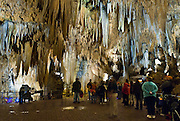 People stroll through pathways in Luray Caverns (originally called Luray Cave), a large commercial cave just west of Luray, Virginia, USA. Discovered in 1878, the Caverns are in the Shenandoah Valley just east of the Allegheny Range of the Appalachian Mountains. The underground cavern system is generously adorned with speleothems (columns, mud flows, stalactites, stalagmites, flowstone, mirrored pools, etc). The caverns are celebrated for performances of the Great Stalacpipe Organ, a lithophone made from solenoid fired strikers that tap stalactites of various sizes to produce tones similar to those of xylophones, tuning forks, or bells.