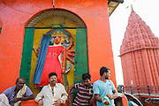 Men near a shrine at Chausatti Ghat by the Ganges river in Varanasi, India.