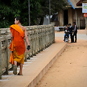 A young novice Buddhist monk in bright orange robes crosses the bridge over the Nam Ou (Ou River) in Nong Khiaw in norther Laos. In the distance at right of frame a few young kids play.. The town's name is sometimes also spelled as Nongkiau, Nong Kiau, or Nong Kiew.
