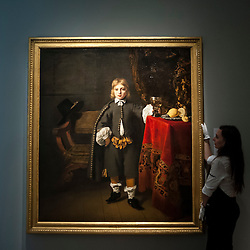 """© Licensed to London News Pictures. 06/07/2015. London, UK.  A Sotheby's technician shows Fernando Bol's """"Portrait of a boy, said to be the artist's son aged 8"""" (est. £2m to £3m) at the preview of Old Masters, British Paintings and Masterworks from the collection of Castle Howard at Sotheby's ahead of the auction on July 8. Photo credit : Stephen Chung/LNP"""